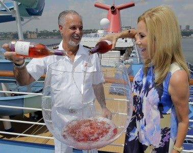 Kathie Lee Gifford celebrates the release of her new wine, GIFFT Pinot Noir Rose, with Carnival Splendor Captain Candeloro Donato, left, as they pour it into a giant wine glass aboard the ship while docked in New York, July 27, 2015. The wine will now be served across the entire fleet.  Carnival Cruise Lines/Ray Stubblebine